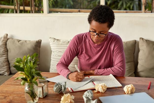 Escritor criativo de pele escura escreve a conclusão do ensaio
