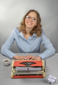 Escritor de óculos atrás de uma máquina de escrever