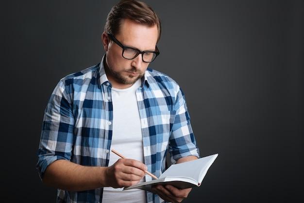 Escritor focado. um cara calmo e dedicado que compila uma agenda enquanto usa seu diário e um lápis para escrever