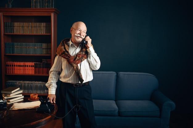 Escritor idoso falando por telefone vintage no escritório em casa. velho de óculos escrevendo romance de literatura em uma sala com fumaça