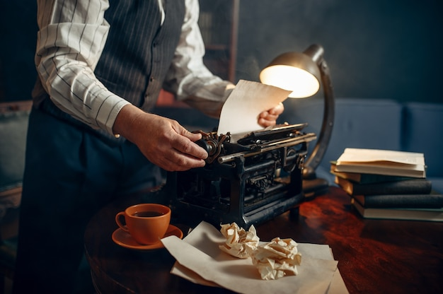 Escritor idoso insere papel na máquina de escrever vintage em seu escritório em casa. velho escreve romance de literatura em uma sala com fumaça, inspiração, café e lençóis amassados sobre a mesa
