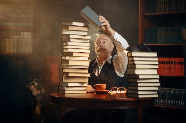 Escritor idoso lê à mesa com uma pilha de livros no escritório em casa. velho de óculos escreve romance de literatura em uma sala com fumaça, inspiração