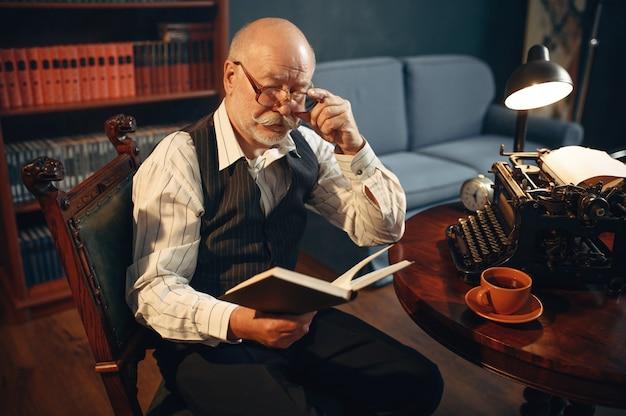 Escritor idoso lê seu trabalho em uma máquina de escrever vintage no escritório em casa. velho de óculos escreve romance de literatura em uma sala com fumaça, inspiração