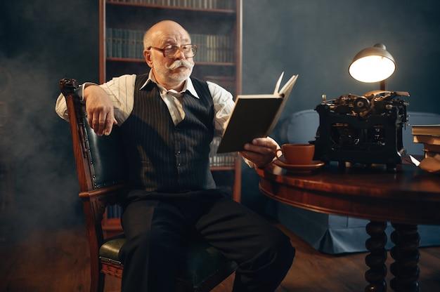Escritor idoso lê seu trabalho em uma máquina de escrever vintage no escritório em casa. velho de óculos escrevendo romance de literatura em uma sala com fumaça