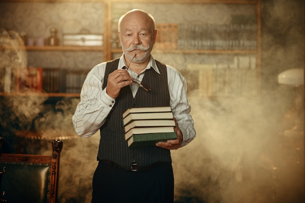 Escritor idoso mantém pilha de livros no escritório em casa. velho de óculos escreve romance de literatura em uma sala com fumaça, inspiração