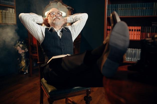Escritor idoso relaxando no escritório em casa. velho de óculos escreve romance de literatura em uma sala com fumaça, inspiração