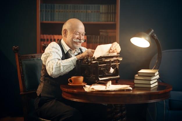 Escritor idoso sorridente trabalha na máquina de escrever retrô no escritório em casa. velho de óculos escreve romance de literatura em uma sala com fumaça, inspiração