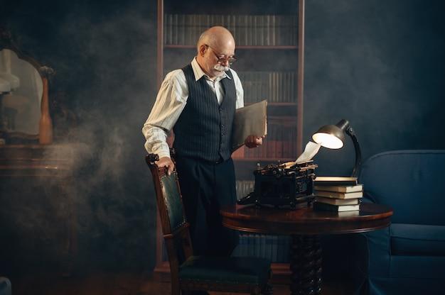 Escritor idoso trabalha em máquina de escrever vintage em seu escritório em casa. velho de óculos escrevendo romance de literatura