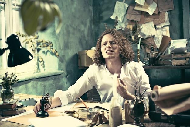 Escritor jovem e bonito sentado à mesa e escrevendo algo em seu bloco de desenho em casa