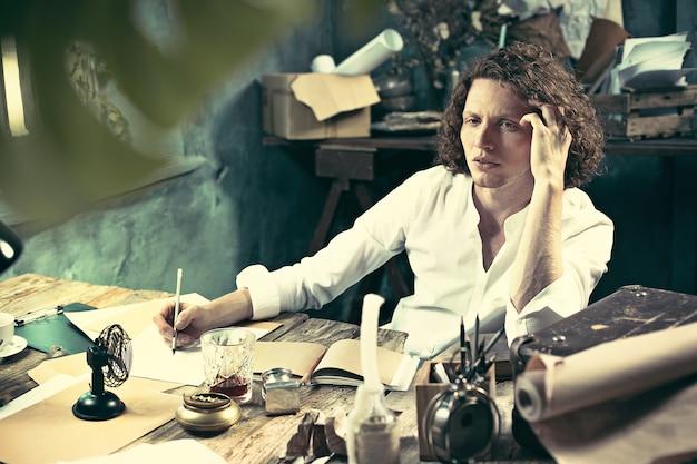 Escritor no trabalho. escritor jovem e bonito sentado à mesa e escrevendo algo em seu bloco de desenho em casa
