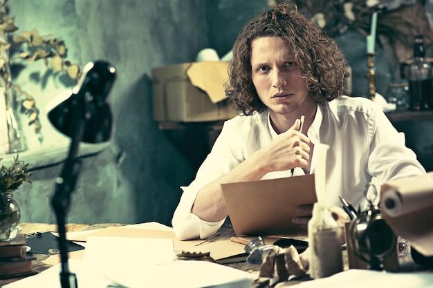 Escritor no trabalho. escritor jovem e bonito sentado à mesa e escrevendo algo em seu bloco de desenho