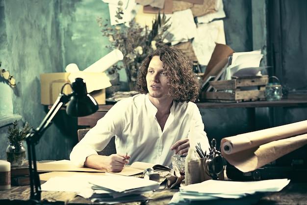 Escritor no trabalho. jovem escritor sentado à mesa e escrevendo algo em seu bloco de desenho em casa