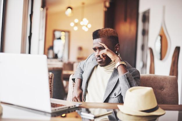 Escritor profissional bonito afro-americano pensativo de artigos populares no blog vestido com roupa da moda