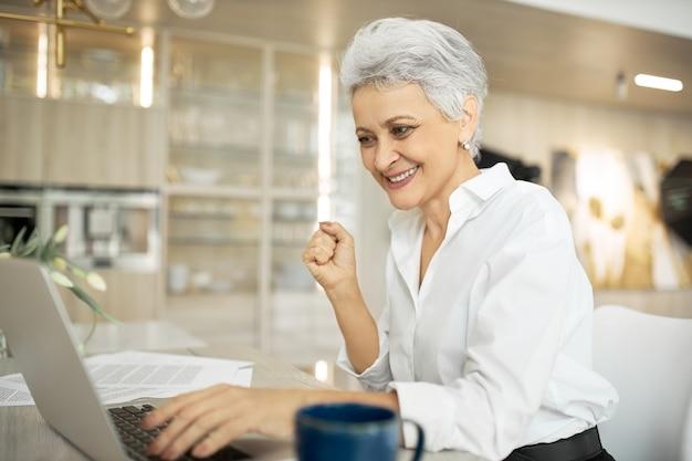 Escritora bem-sucedida, madura, sentada à mesa com um computador portátil, papéis e uma xícara de café, com uma expressão facial feliz porque conseguiu terminar o trabalho a tempo