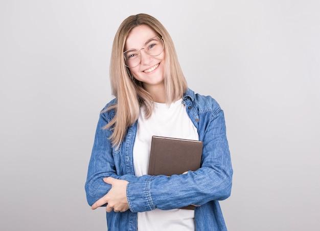 Escritora de mulher feliz com cabelo loiro, óculos e uma camisa jeans tem um livro escrito nas mãos e sorri. dia internacional dos escritores