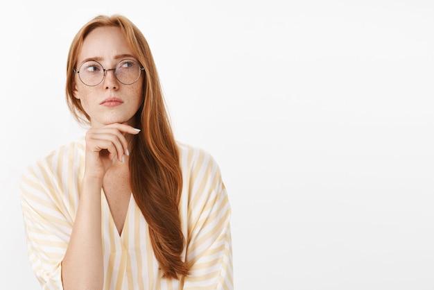 Escritora preocupada, pensativa e concentrada, criativa, com cabelo ruivo e sardas nos óculos e uma blusa amarela da moda, em pé na pose de hmm, parecendo duvidosa e focada tocando o queixo