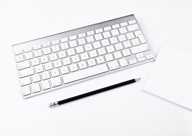 Escritório branco com teclado e lápis preto