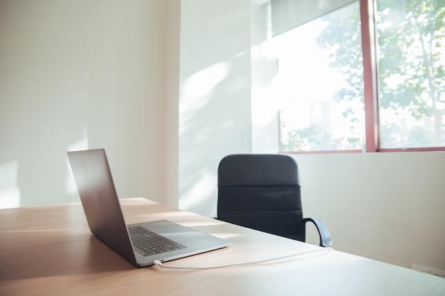 Escritório brilhante com luz natural e laptop