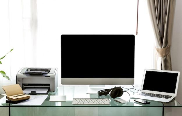 Escritório com um computador e uma mesa de vidro
