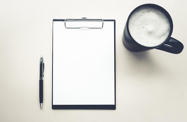 Escritório com vista de cima com bloco de notas, caneta e café em fundos brancos