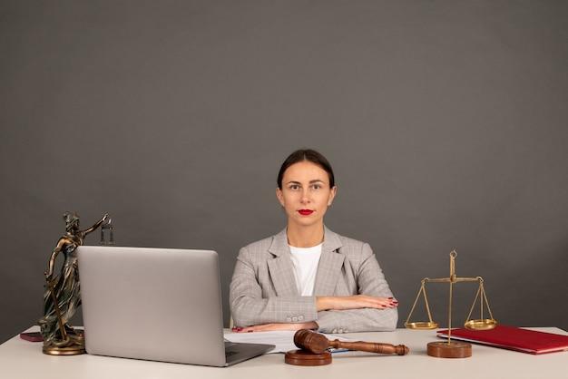 Escritório de advocacia. estátua da justiça com balança e advogado trabalhando em um laptop. conceito jurídico, conselho e justiça