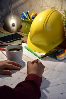 Escritório de arquitectura com desenhos, computação e trabalho de pessoa