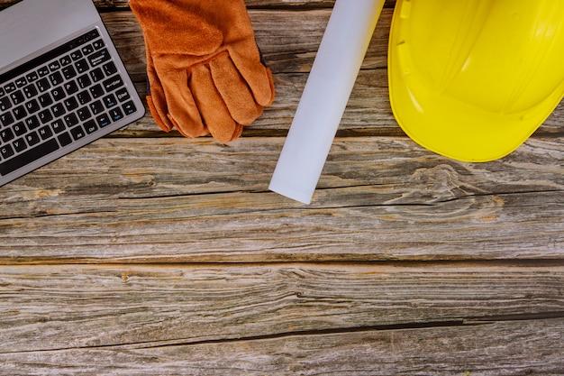 Escritório de construção trabalhando o teclado do computador com plantas no conjunto de vestuário de trabalho protetor em luvas protetoras de capacete amarelo