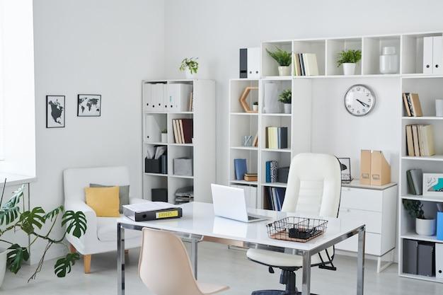Escritório de empresário com mesa, poltrona de profissional, cadeira para clientes, prateleiras, relógio, planta verde e duas fotos na parede