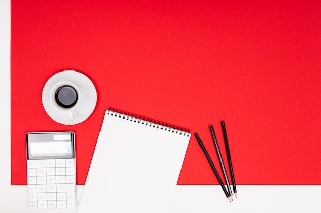 Escritório de espaço de trabalho. calculadora e artigos de papelaria em vermelho com espaço de cópia
