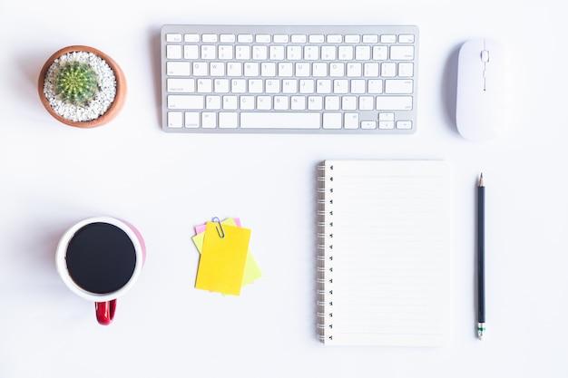 Escritório de mesa branca com laptop, smartphone e outros suprimentos de trabalho com café