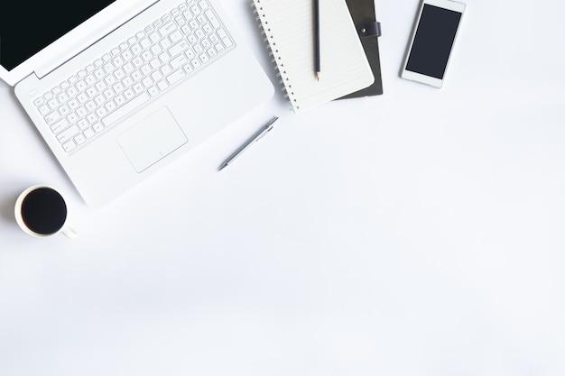 Escritório de mesa branca na configuração plana. vista superior em elementos essenciais da tabela de mesa.