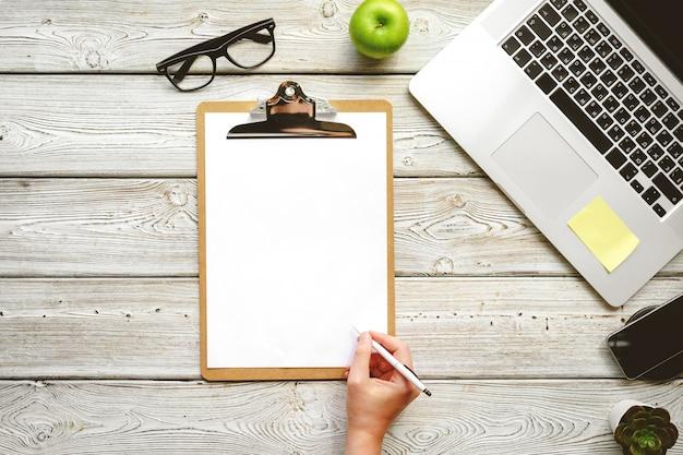 Escritório de postura plana, espaço de trabalho com mão feminina e laptop