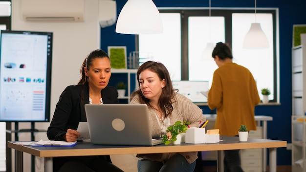 Escritório do gerente e diretor criativo, trabalhando em um escritório moderno, usando o laptop sentado na mesa, desenvolvendo a ideia de inicialização. equipe diversificada de executivos analisando relatórios financeiros da empresa no computador