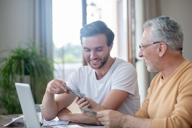 Escritório em casa. dois homens sentados à mesa e trabalhando em um laptop