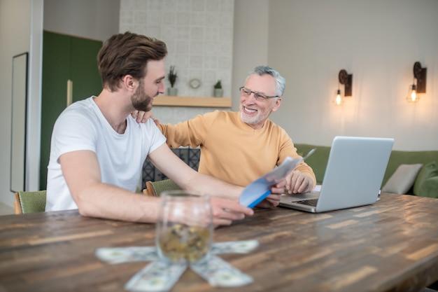 Escritório em casa. dois homens trabalhando em um escritório doméstico e parecendo envolvidos