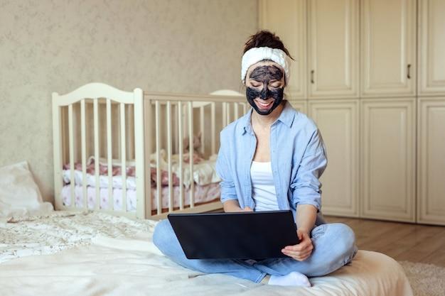 Escritório em casa e garota freelance em roupas para casa de uma máscara de carvão no rosto trabalha sentado em casa na cama.