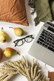 Escritório em casa mesa mesa área de trabalho com laptop, óculos, grinalda de palha de trigo, folhas secas de outono, peras, cobertor, travesseiro. postura plana