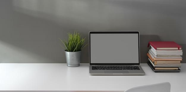 Escritório em casa mínimo com laptop de tela em branco aberto, uma pilha de livro e pote de árvore