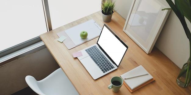 Escritório em casa mínimo com laptop de tela em branco aberto