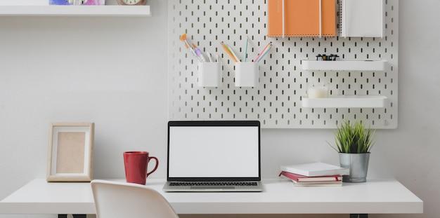 Escritório em casa mínimo com o computador portátil de tela em branco aberto com estacionário