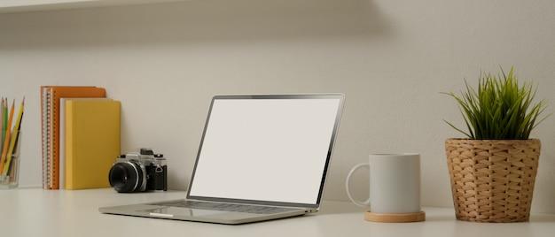 Escritório em casa moderno com mock up laptop, câmera, xícara, artigos de papelaria, livros e decorações na mesa branca
