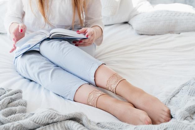 Escritório em casa. planejamento do dia da manhã. mulher sentada na cama e revisando o diário. close-up pés em meias arrastão.