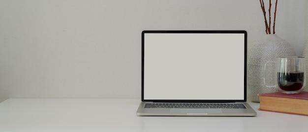 Escritório em casa simples com laptop, livro, xícara de café, decorações e espaço de cópia na mesa branca