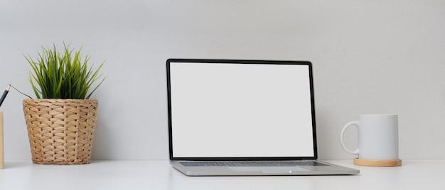 Escritório em casa simples com mock up laptop, xícara de café, vaso e artigos de papelaria na mesa branca