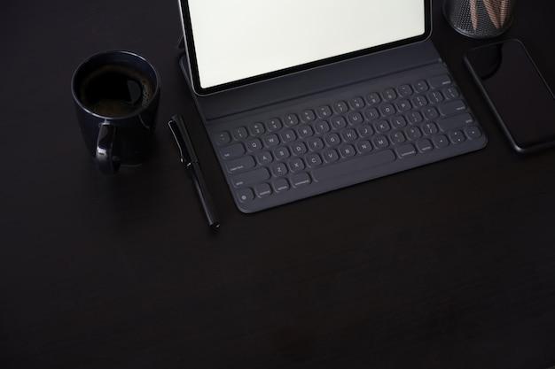 Escritório espaço de trabalho de madeira escura com tablet, material de escritório e espaço de cópia