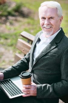Escritório externo. homem de negócios maduro e jovial usando laptop enquanto olha para a câmera