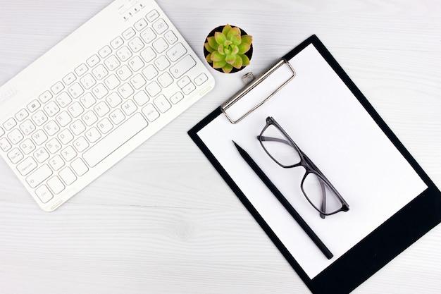 Escritório flatlay com teclado branco, óculos de leitura, animal de estimação e notebook