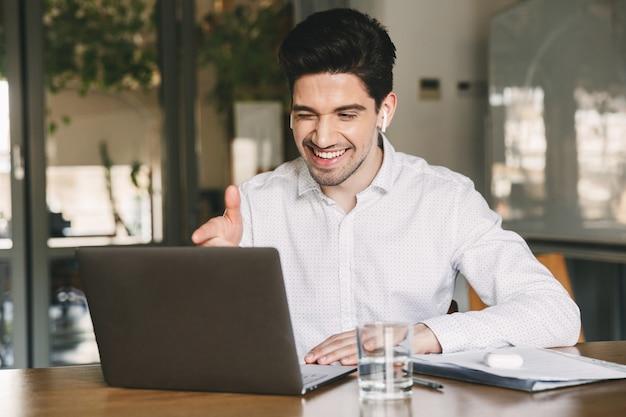 Escritório jovem vestindo uma camisa branca e um fone de ouvido sem fio sorrindo enquanto está sentado à mesa no escritório e apontando o dedo para a tela do laptop durante a videochamada ou chat