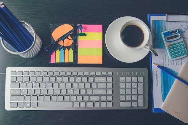 Escritório laptop negócios documento financeiro gráfico e gráfico na mesa de madeira com uma xícara de café. laptop de computador notebook plana leigos na mesa de escritório. nenhuma maquete de gráfico de negócios de pessoas no espaço de trabalho de negócios