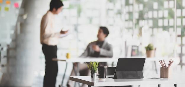 Escritório moderno com tablet e material de escritório na mesa com pessoas de negócios em segundo plano